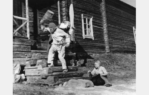 Juha (Eino Kaipainen) riehuu kiulu kädessään. Häntä pelkäävät Juhan äiti (Annie Mörk) ja Marja (Elina Pohjanpää).