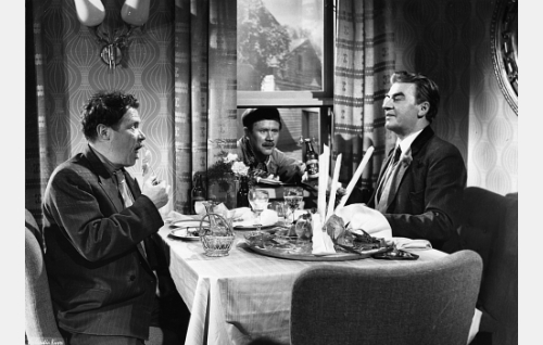 Teurastaja Eemeli Saarikko (Oke Tuuri) ja paroni Moppe Grafvenhjelm (Joel Rinne) illallisella. Ikkunasta kurkistaa Mopen toveri Ville (Hannes Häyrinen).