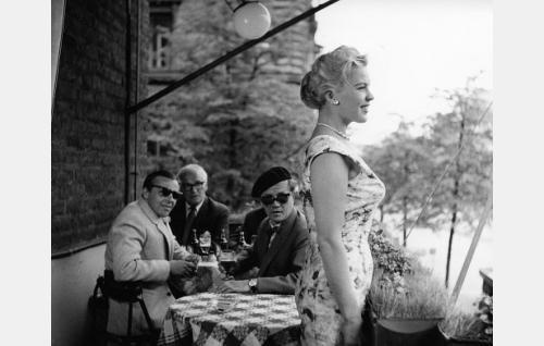Rouva Aalto (Tuija Halonen) ravintola Klaus Kurjen parveketerassilla, ihailijoinaan vasemmalta tuomari Kaius Kannisto (Pehr-Olof Sirén), majuri (Tauno Majuri) ja diplomi-insinööri Riipinen (Hannes Häyrinen).