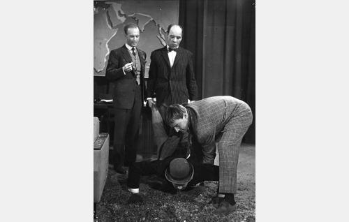 Toimitusjohtaja Kurt Lööperi (Kurt Ingvall) katselee kun hänen apulaisensa Körmy (Uljas Kandolin) ja Liukas (Åke Lindman) käsittelevät Isaskar Keturia (Hannes Häyrinen).
