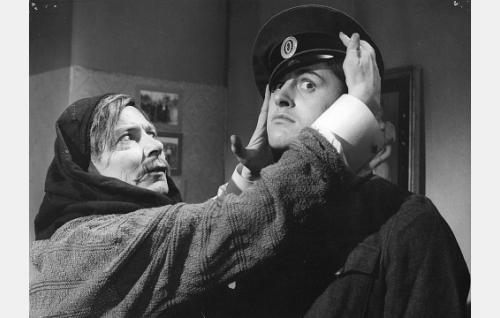 Valokuvaaja Herman Ahlroos (Toivo Mäkelä) asettelee sotilaan (Esko Salminen) hattua valokuvaa varten.