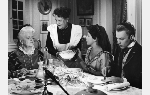 Pöydän ääressä paronitar Louise Ehrenheim (Ruth Snellman), Helena Ehrenheim (Pirkko Mannola) ja Paul von Holden (Stig Fransman). Heille tarjoilee Loviisa (Siiri Angerkoski).