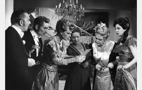 Helenan kirjelappu on löytynyt ja herättää kummastusta. Vasemmalta: kamreeri Brynolf Pedantzius (Esko Mannermaa), maisteri Henryk Södersvans (Esa Saario), Gisela von Holden (Rauha Rentola), ompelija (Elin Aaltonen), Alma Wahl (Kaisu Leppänen) ja Betty Wahl (Rose-Marie Precht).
