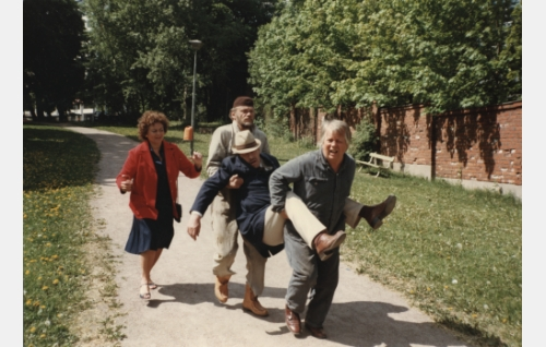 Sörsselssön (Simo Salminen, oik.) ja Härski-Hartikainen (Spede Pasanen) kantavat pyörtynyttä vuorineuvos Tuuraa (Tapio Hämäläinen) sairaalaan vuorineuvoksettaren (Marjatta Nordberg) seuratessa.