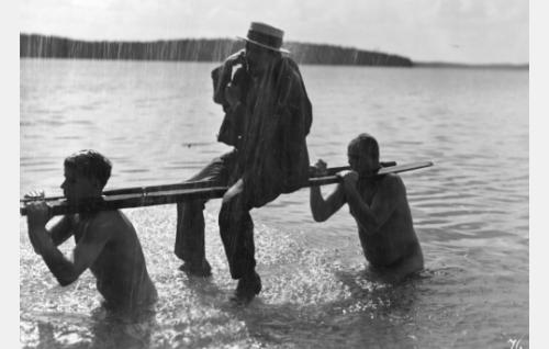 Avuliaat toverukset Himanen (Joel Rinne) ja Kehkonen (Yrjö Tuominen) kantavat asemapäällikön (Kaarlo Saarnio) rantaan veneen karahdettua kiville.