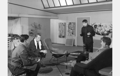 """Kuulusteluhetki taiteilija Kuurnan ateljeessa. Oik. komisario Palmu (Joel Rinne), taiteilija Kurt Kuurna (Pentti Siimes), rouva Skrofin veljenpoika Kaarlo Lankela (Saulo Haarla) ja komisarion apulainen Virta (Matti Ranin). Taustalla vasemmalla oleva taulu nähtiin myös elokuvassa <i>Alaston malli karkuteillä</i> (1953) tuolloin """"Alaston totuus"""" nimisenä."""