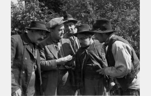 Freybergin työpäällikkö Eetvart Männistö (Paavo Costiander, toinen vas.) värvää apujoukkoja hämäriin puuhiinsa. Costianderista vasemmalla Onni Veijonen ja oikealla puolen Kaarlo Saarnio, Kalle Grönfors ja tunnistamaton. Grönfors muutti vuonna 1935 sukunimensä Viherpuuksi.