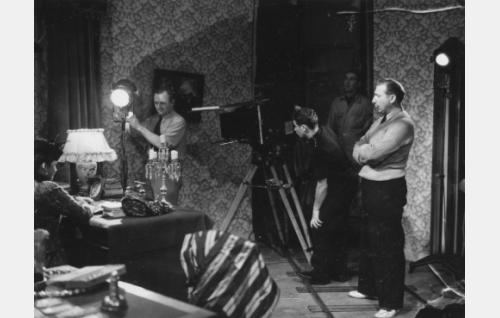 Kuvaaja Charlie Bauer suuntaa valoja kohti Tuulikki Paanasta. Äärimmäisenä oikealla seisoo ohjaaja Risto Orko. Upouuden Debrie-kameran vieressä kamera-apulainen Erkki Kokkonen, takana äänitysassistentti Eino Oksanen.