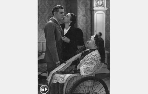 Laamannitar Harmaalahti (Emmi Jurkka) suutelee miestään Robert Harmaalahtea (Tauno Palo) senattoorska Agnes Harmeliuksen (Elsa Rantalainen) tutkivan katseen alla.
