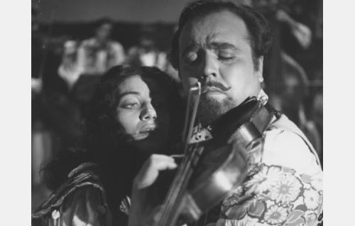 """""""Mustalaisorkesterina"""" esiintyvä viihdeorkesteri, jossa on viulusolisti, esittää sikermän mustalaissävelmiä. Pentti Tuominen viulistina."""