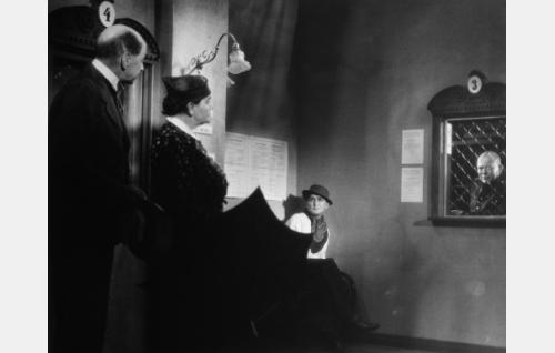 Herra Lahtisen appivanhemmat (Lauri Korpela, Hertta Leistén) etsivät kadonnutta säveltä löytötavaratoimistosta. Oikealla panttivirkailija (P. Tiilikainen), keskellä äänensä kadottanut laulaja (Albert Saloranta).