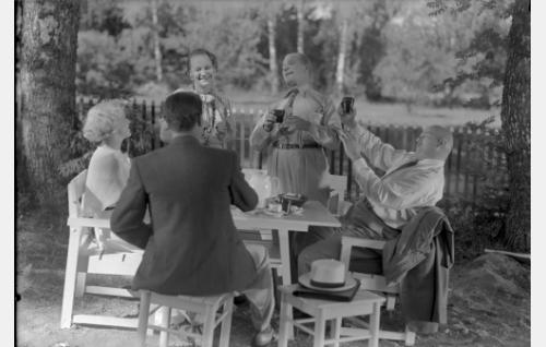 Iloinen seurue juhlii Maresten kesähuvilan pihalla. Vasemmalta Kirsti Mares (Ansa Ikonen), insinööri Karma (Jalmari Rinne, selin), täysihoitolan emäntä Josefine (Martta Suonio), taiteilija Into Sydänmurto (Uuno Laakso) ja tuomari Salomon Mares (Yrjö Tuominen).
