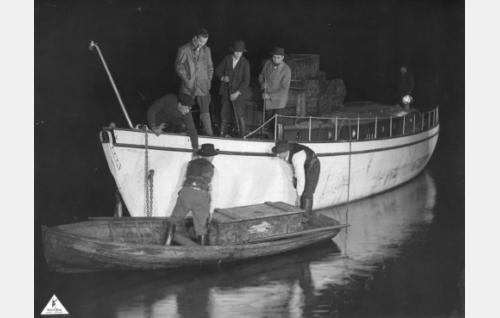 Aktivistit lastaavat yön pimeydessä aselaiva John Graftonista hankittuja kivääreitä. Kannella toinen vasemmalta Antti (Aarne Leppänen).