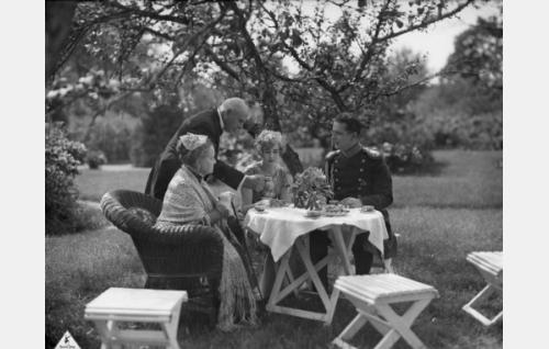 Kahvihetki Cederströmien puutarhassa: rouva Cederström (Katri Rautio), hovimestari (tunnistamaton näyttelijä), Louise Cederström (Elsa Segerberg) ja ratsumestari Karl Gustaf Cederström (Helge Ranin).