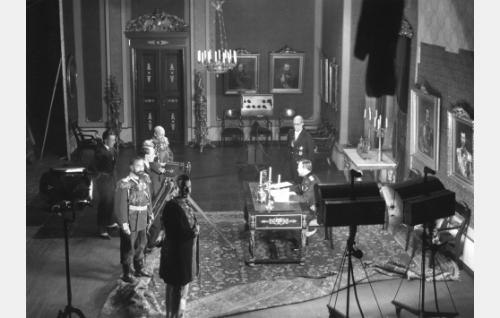 Työkuva: keisari Nikolai II allekirjoittaa helmikuun manifestin. Henkilöt vasemmalta ohjaaja Carl von Haartman, näyttelijä William Räisänen, kuvaaja Eino Kari, näyttelijät Aku Korhonen, Uuno Montonen, A. Karsten ja Torsten Leistén. Leistén tunnettiin myöhemmin Topo Leistelänä.