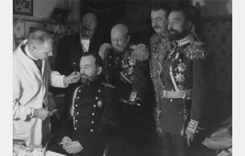 Hannes Kuokkanen naamioi A. Karstenia keisari Nikolai II:ksi. Taustalla näyttelijät Torsten Leistén, Aku Korhonen, Uuno Montonen ja William Räisänen.