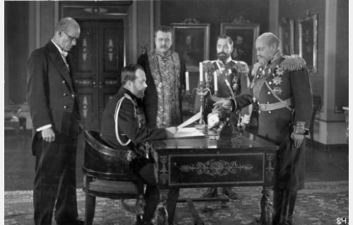 Keisari allekirjoittaa helmikuun manifestin. Vasemmalla yliprokuraattori Pobjedonostjew (Torsten Leistén), Nikolai II (A.Karsten), valtiosihteeri von Plehwe (Uuno Montonen), kenraali Kuropatkin (William Räisänen) ja kenraalikuvernööri Bobrikoff (Aku Korhonen).