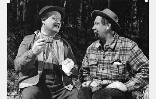 Kaksi vanhaa tukkijätkää, vuorineuvos Daniel Saarinen alias Taneli Saari (Ossi Elstelä) ja Jaakko Naskali alias Moterni-Jaska (Armas Jokio).