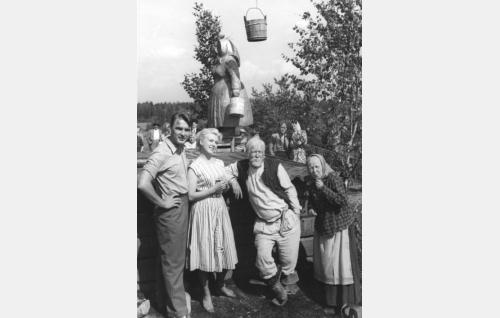 Juhannusjuhlat Kankkulan kaivolla. Patsas on paljastettu ja ämpäri vihitty. Henkilöt vasemmalta: vallesmannin pojanpojanpojanpoika Lauri (Ismo Kallio), vanhanisännän tyttärentyttärentyttärentytär Leena (Leni Katajakoski), Tippavaaran vanhaisäntä (Oke Tuuri) sekä Tippavaaran mummu (Henny Waljus).
