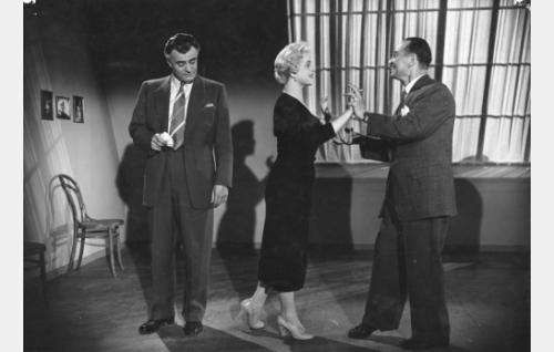 Tanssinopettaja Lorenzo (Akseli Vuorisola, oik.) opettaa Babsille (Hillevi Lagerstam) samban askeleita. Mauri Pekanpää (Tauno Palo) seuraa sivulta.