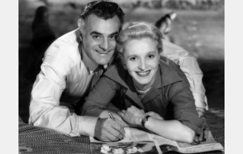"""Isän vanha ja uusi -elokuvan mainoskuva. Idean kuvaan antoi Ansa Ikosen ja Tauno Palon ensimmäisestä yhteisestä elokuvasta Kaikki rakastavat (1935) otettu valokuva, joka näkyy myös tässä kuvassa elokuvalehden aukeamalla. Tämän """"20 vuotta myöhemmin"""" -asetelman on ottanut valokuvaaja Päivi Kosonen, lempinimeltään """"Miss Kodak""""."""