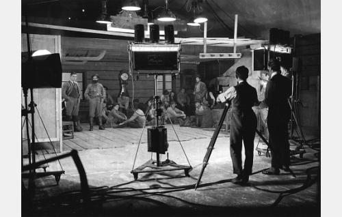 Vironkadun studioon rakennettu Nuottaniemen tupainteriööri. Kameran takana on kuvaaja Kurt Jäger ja hänen oikealla puolellaan ohjaaja Erkki Karu. Kuva-alassa seisovat vasemmalla Oiva Soini ja Jaakko Korhonen ja oikealla Joel Rinne.