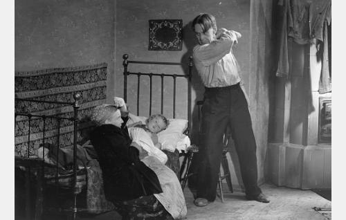 Juoppo työmies Vesanen (Arvo Lehesmaa) uhkailee vaimoaan (Henny Waljus) ja sairasta lastaan.