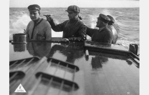 Pistoolilla uhaten salakuljettajien päällikkö Jysky (Axel Slangus) pakottaa kalastaja Eerikin (Wilho Ilmari) ohjaamaan veneen myrskyävälle merelle.