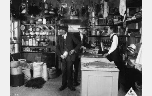Salakauppaa harjoittava kauppias Strutberg (Alarik Korhonen) tiskinsä takana.