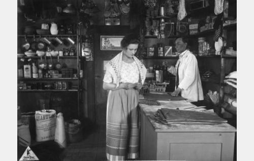 Salakauppaa harjoittava kauppias Herman Strutberg (Alarik Korhonen) liehittelee luotsivanhimman tytärtä Kirsti Bomania (Irja Lindström).