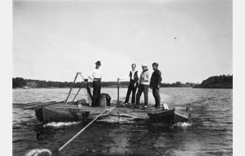 Liikkuvan moottoriveneen kuvaamista varten kahden soutuveneen varaan rakennettiin hinattava lautta. Vasemmalta kuvaaja Frans Ekebom, ohjaaja Erkki Karu, kuvaaja Kurt Jäger ja kuvausapulainen Armas Fredman.