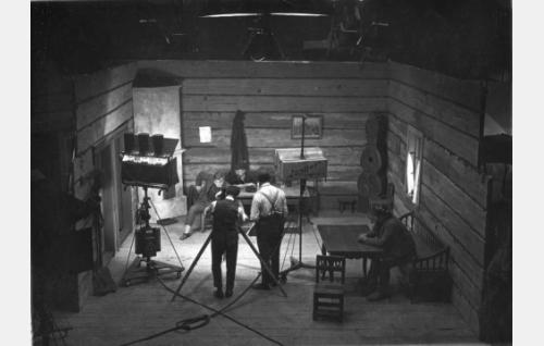 Nummisuutarien kapakkakohtaus Vironkadun studiossa 1923. Kameran takana Frans Ekebom ja Erkki Karu, pöydän ääressä Antero Suonio ja Aku Käyhkö, sivupenkillä Juho Puls.