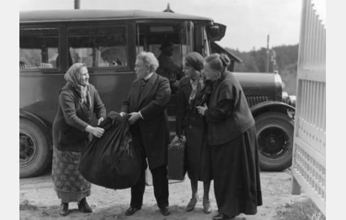 Rovasti (Hemmo Kallio) ja ruustinna (Katri Rautio, oik.) ovat Elina-tytärtään (Iris Knape) vastassa. Rovasti on epähuomiossaan vienyt toisen linja-automatkustajan (Mimmi Lähteenoja) matkanyytin.