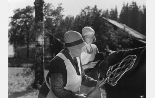 Ruustinna (Katri Rautio) ja pappilan sisäkkö Alina (Helena Koskinen) vaatteita tomuttamassa. Rooli oli Helena Koskisen ensimmäinen, pääosassa hän oli saman vuoden toisessa elokuvassaan <i>Tukkipojan morsian</i>.