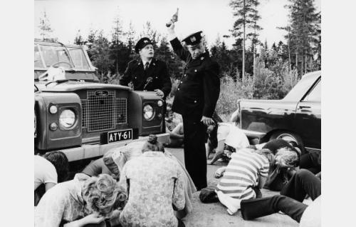 Poliisit ja heidän pysäyttämänsä liftaajia pursuava auto. Poliisien rooleissa (Oiva Tainio, pistooli kädessä) ja Arvo Ensio Kivimaa (Matti Vihola).