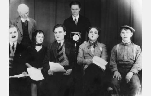 """""""Taka-Peltolan ratioasema"""" esitti humoristisena revyynumerona Romeon ja Julian. Juliaa esitti Elsa Närhi (istumassa toinen vas.), Romeota Hemmo Airamo (Elsa Närhin oikealla puolella). Mikrofonin takana keskellä seisoo ohjaaja Yrjö Nyberg. Mikrofonista oikealle istuvat Onni Veijonen ja Paavo Sainio, äärimmäisenä vasemmalla on Edvin Laine."""