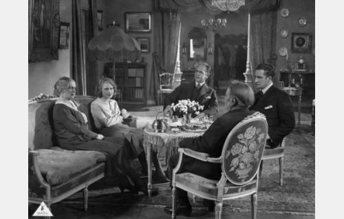 Kartanon salissa kahvipöydän ääressä Erkin äiti (Hilja Jorma), Leena (Helena Koskinen), Erkin isä (Thorild Bröderman), Erkki (Urho Somersalmi) ja Leena isä (Hemmo Kallio, selin).