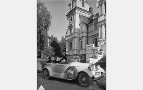 Tukkipoika Erkki (Urho Somersalmi), rikkaan kartanonomistajan poika, vie Leenan (Helena Koskinen) ja tämän Kustaa-isän (Hemmo Kallio) tutustumaan kotiinsa. Ohjaaja Erkki Karun Lincoln-auto on Hollolan Pyhäniemen kartanon päärakennuksen edustalla kesällä 1931.